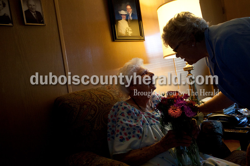 "Dave Weatherwax/The Herald<br /> ""Oh, aren't they pretty,"" Elvera Gress of Jasper, left, said after receiving her weekly bouquet of zinnias from Jorean Hoffman of Jasper on Tuesday morning at Gress' home. Every other day, and sometimes daily, Hoffman delivers bouquets of flowers she grows herself to the homes of individuals like Gress, who is 97-years-old, that can no longer get out of their homes. After delivering the flowers, Gress and Hoffman sat down to play the card game Rummy."
