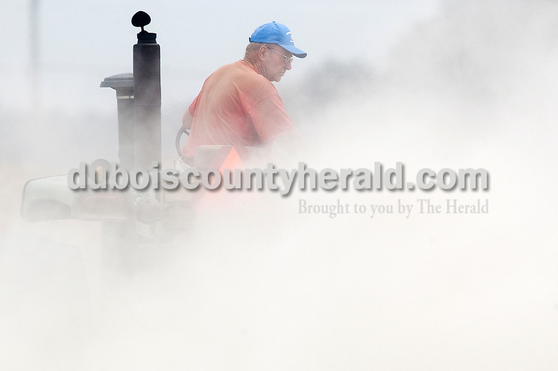 Dave Weatherwax/The Herald<br /> A large cloud of dust was kicked up as Allen Brescher of Ireland started down a new row  while brush hogging leftover corn stalks in a field near Ireland on Monday morning. Allen said he was doing the work for his son, Mark, who planted the corn. On Saturday, they shelled the corn and put down rye seed with the plans to grow and cut rye with the corn silage to make feed for Mark's cattle.