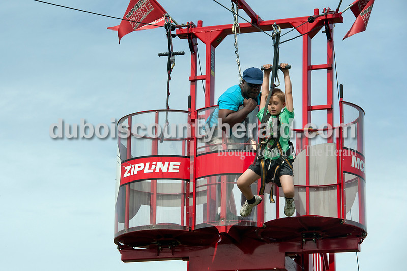 Olivia Corya/The Herald<br /> Issac Fuhrman of Ferdinand, 9, took the plunge on the zip line after being encouraged to give it a try by attraction worker Dennis Handley of Toledo, Ohio, at the Ferdinand Folk Festival on Saturday.