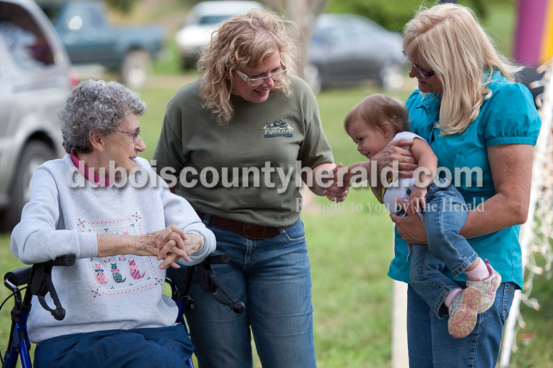 "Olivia Corya/The Herald<br /> Self described ""life long friends"" Doris Peters, far left, Christy Miller, center, and Suzette Bolin, right, all of Holland, played with Bolin's granddaughter Madison Richardson of Stendal, 1, at the Holland Community Fest on Saturday."