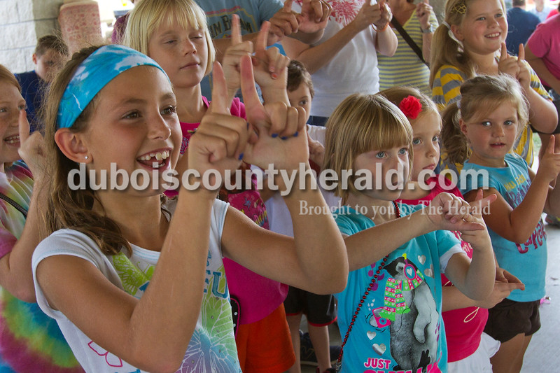 Olivia Corya/The Herald<br /> Mikalyn Meyer of Ferdinand, 8, left, mimicked hand motions along with Abbagail Collignon of Ferdinand, 5, right of Mikalyn with purse strap, during a storytelling performance for children at the Ferdinand Folk Festival on Saturday.
