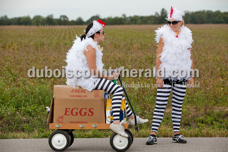 Rachel Mummey/The Herald<br /> Ashley Hohler of Jasper rested for a moment on her cooler, which was disguised as a box of eggs with her teammate Gina Beyke also of Jasper during the third annual Irish Road Bowling competition in Ireland on Saturday. Participating teams had the option of dressing in costume and decorating their coolers for prizes as part of the competition.