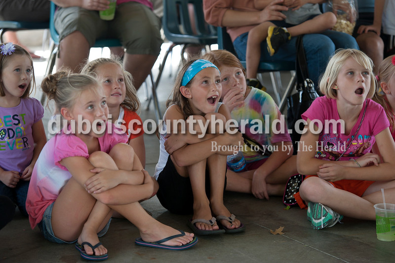 Olivia Corya/The Herald<br /> Amy Wahl, 8, far left in front row, Rayven Meyer, 5, right of Amy, Mikalyn Meyer, 8, center with headband, Ali Brandes, 8, wearing tie-dye, and Philicity Collignon, 8, all of Ferdinand, watched a storytelling performance for children at the Ferdinand Folk Festival on Saturday.
