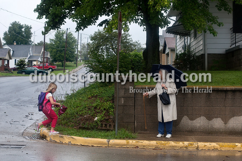 Dave Weatherwax/The Herald<br /> Grace Jarboe of Jasper, 7, left, ran to her grandmother Joan Jarboe of Jasper who was waiting under an umbrella at the corner of 15th and Leopold Streets in Jasper on Monday afternoon for Grace to get off of the school bus. Since it was raining, Joan said she thought she'd meet Grace at the stop with an extra umbrella in case she hadn't taken one to school.