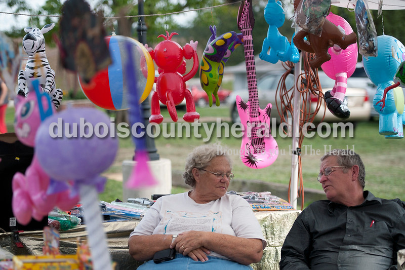 Olivia Corya/The Herald<br /> Fred and Shila Webster of Bicknell chatted as they waited for customers at their prize booth during the Holland Community Fest on Saturday. The husband and wife work at the florist shop they own in Bicknell on week days, but on weekends travel to festivals, which they enjoy because they love interacting with kids.