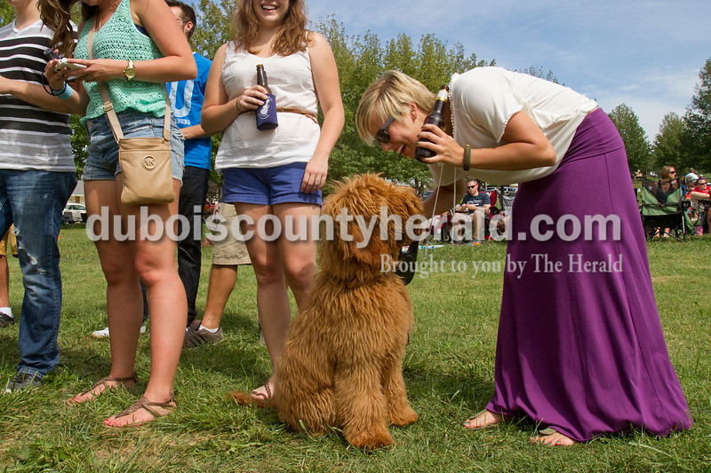 Olivia Corya/The Herald<br /> Danielle Glick of Indianapolis, 23, whose boyfriend is from Ferdinand, played with her dog Umphrey while watching a performance at the Ferdinand Folk Folk Festival on Saturday. She came to the fest with a group of friends, most of whom were from Ferdinand.