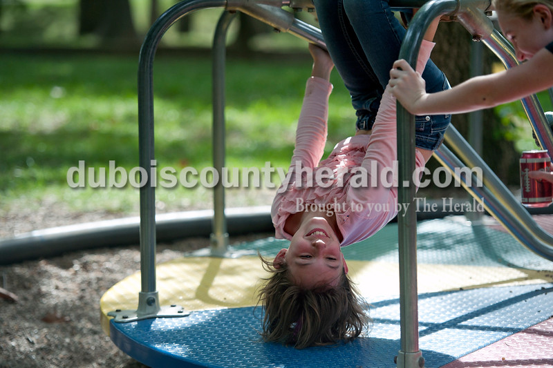 Olivia Corya/The Herald<br /> Luxey Neukam of Huntingburg, 10, hung upside down on the merry-go-round with her friend Macee Long of Wadesville, 11, at the Holland Community Fest on Saturday.