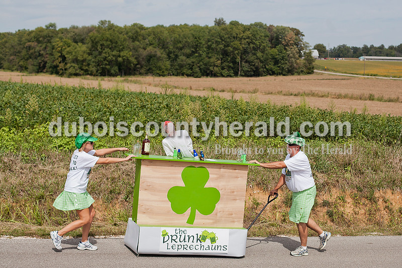 Rachel Mummey/The Herald<br /> Sherri Mendel and Roy Main, both of Ireland, wheeled their cooler, decorated as a bar, down the road during the Third annual Irish Road Bowling competition on Saturday. Their spouses, Curt Mendel and Shelly Main were also on their road bowling team.