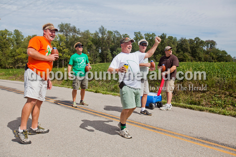 Rachel Mummey/The Herald<br /> Craig Greulich of Ireland, left, cheered on Jerry Himsel of Ireland, center, after a successful throw during third annual Irish Road Bowling competition in Ireland on Saturday. Also with them are members of Greulich's team, 4 Fine O'Fellas, Todd Ofer Ireland, second from left, Neil Verkamp Ferdinand, second from right. and non-teammate but moral supporter Dan Cooley Jasper, far right. Teammate Brian Seibert Ireland was not pictured.
