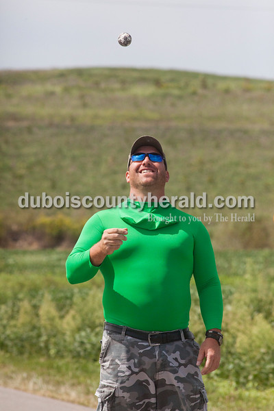 Rachel Mummey/The Herald<br /> Chad Hardin of Ireland tossed the five-pound steel ball used for the Irish Road Bowling competition into the air as he waited for his turn to throw in Ireland on Saturday. Hardin's team, who all showed up in green spandex suits, was fittingly called The Green Men.