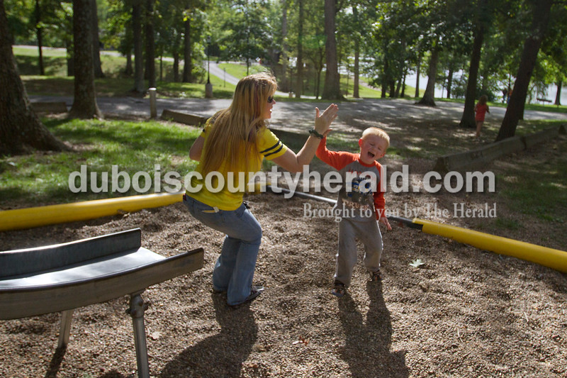 Olivia Corya/The Herald<br /> Christopher Green of Jasper, 5, high fived his mom Jessie after convincing her to go down a slide on the playground during the Holland Community Fest on Saturday.