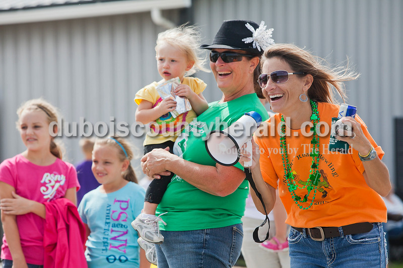 Rachel Mummey/The Herald<br /> Jody Verkamp of Jasper, right, laughed with Jane Renner of Ireland, holding her 22-month-old granddaughter Anna Renner, after speaking into a megaphone to her teammates down the road Third annual Irish Road Bowling competition on Saturday.
