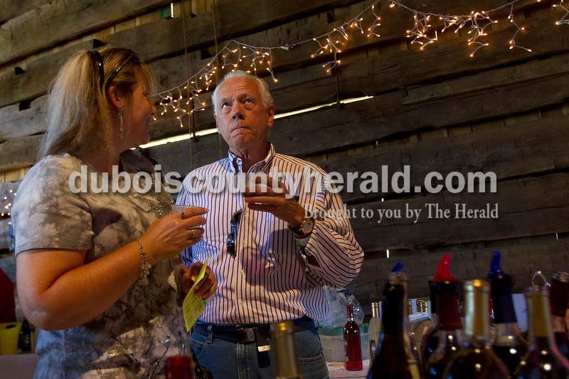 """Olivia Corya/The Herald<br /> Paul Little of Jasper and his friend LeAnne Sitzman of Loogootee sampled wine from Winzerwald Winery during the sixth annual Riverwalk Taster's Fest, a fundraiser for Anderson Woods, in Jasper on Saturday. Anderson Woods is a camp with people for mental or physical disabilities. Sitzman says they came to try the different foods, but """"lots of wine, that's the main thing!"""""""