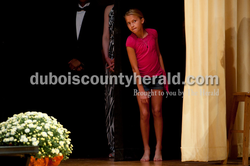 Olivia Corya/The Herald<br /> Sidney Bartelt of Huntingburg, 11, peaked from behind the curtain to get a glimpse of one of the contestants during the Herbstfest Queen Pageant in the Southridge High School auditorium on Sunday. Sidney's mother was a co-coordinator of the event.