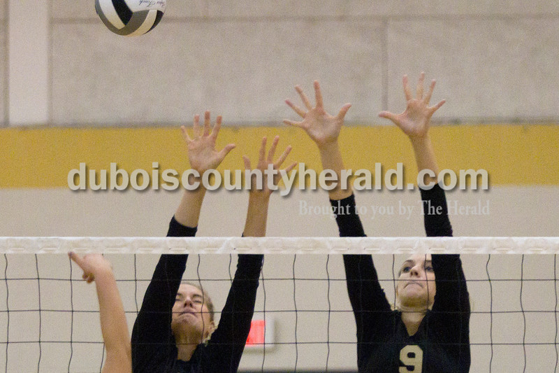 Olivia Corya/The Herald<br /> Jasper's Abby Rogers, left, and Shelby Merder attempted to spike the ball as they played against Evansville Central High School during the Jasper invitational at Jasper High School on Saturday.
