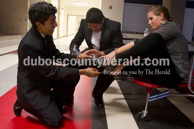 Olivia Corya/The Herald<br /> Irvin Rocha, 18, left, and Santiago Nunez, 17, both of Huntingburg, helped Herbstfest Queen Pageant contestant Joyce Marie Lawrence of Huntingburg, 18, tuck her pants into her shoes before the show started at Southridge High School on Sunday.