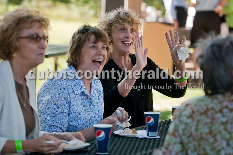 """Olivia Corya/The Herald<br /> Susan Leonard waved to friends as she sat with friends Lynn Foy, center, and Carol Dooley, far left, all of Jasper, during the sixth annual Riverwalk Taster's Fest, a fundraiser for Anderson Woods camp, in Jasper on Saturday. They were eating apple strudel with cinnamon ice cream from Schnitzelbank, of which Foy says she """"could just have a bucket!"""""""