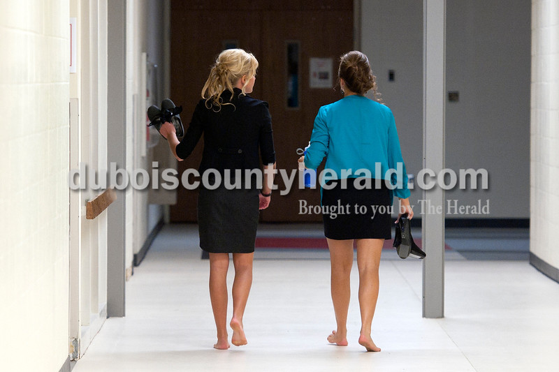Olivia Corya/The Herald<br /> Riley Gasser, left, and Kaylyn Long, both of Huntingburg, 16, gave their feet a break as they walked backstage before the Herbstfest Queen Pageant in the Southridge High School auditorium on Sunday.