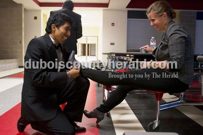 Olivia Corya/The Herald<br /> Irvin Rocha, 18, helped Herbstfest Queen Pageant contestant Joyce Marie Lawrence, 18, tuck her pants into her shoes before the show started at Southridge High School on Sunday. Both are from Huntingburg.