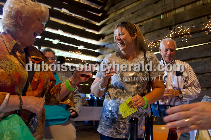 Olivia Corya/The Herald<br /> Judy Thomas-Hall of Derby, LeAnne Sitzman of Loogootee, and Paul Little of Jasper, left to right, sampled wine from Winzerwald Winery during the sixth annual Riverwalk Taster's Fest, a fundraiser for Anderson Woods, in Jasper on Saturday. Anderson Woods is a camp with people for mental or physical disabilities.