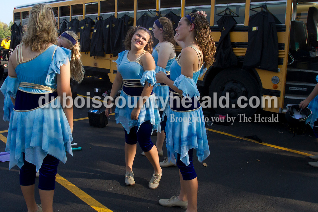 Olivia Corya/The Herald<br /> Jasper color guard member Cassandra Gregory, second from left, complemented the hair of Mackenzie Loomis, right, as they got ready before competing in the ISSMA band districts at Jerry Brewer Alumni Stadium in Jasper on Saturday. Both girls are sophomores.