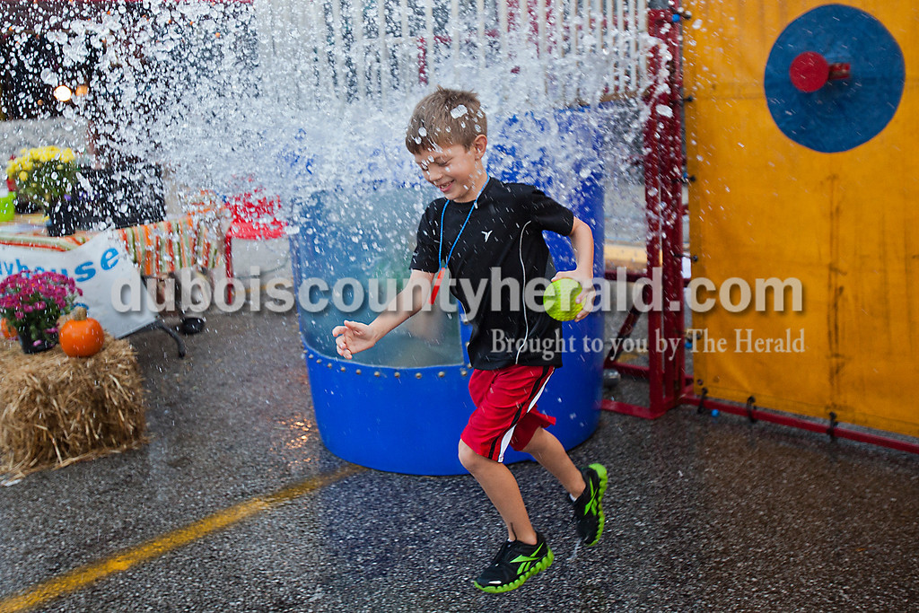 Rachel Mummey/The Herald<br /> Owen Morrison of Huntingburg, 7, darted splashing water from the dunk tank at the Herbstfest on Friday. He missed the target but volunteers let him push the button anyway.