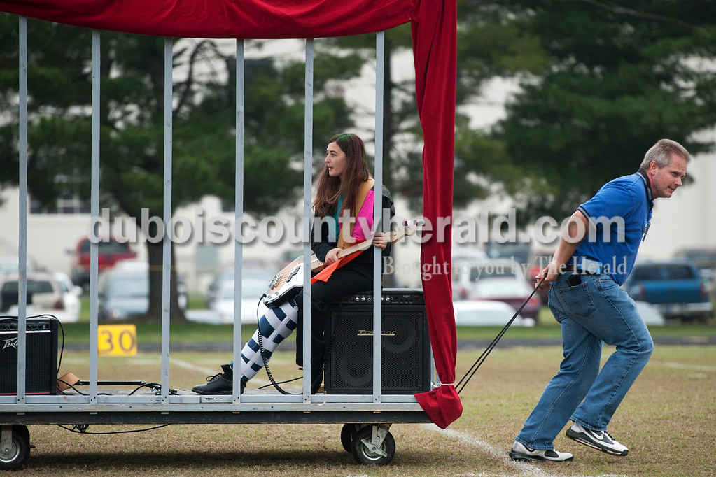 Olivia Corya/The Herald<br /> Pit crew volunteer Wayne Mehringer of Dubois pulled Northeast Dubois marching band member Bethaney Haley, junior, off the football field where her school just performed for the ISSMA band districts at Jerry Brewer Alumni Stadium in Jasper on Saturday. Haley couldn't march because of a leg injury, so she sat behind a prop cage that was part of their psychotic carnival theme.