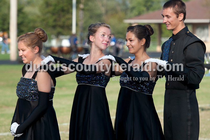 Olivia Corya/The Herald<br /> Jasper's drum majors Courtney Hayden, junior, Avery Charron, junior, Olivia June, junior, and Zach Grewe, senior, left to right, gave each other neck massages as they waited to compete at the ISSMA band districts at Jerry Brewer Alumni Stadium in Jasper on Saturday.