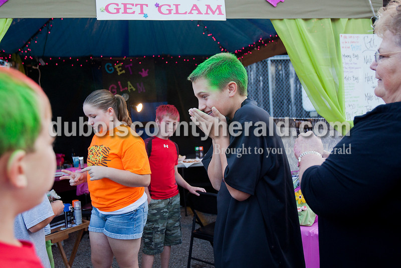 Rachel Mummey/The Herald<br /> Brody Voegerl of Huntingburg, 13, second from right, couldn't hide his smile after getting his hair sprayed green by by Nancy Begle of Santa Claus, far right, with Gabe Wilkey of Huntingburg, 10, center, while Shana Ramsey of Holland, 13, left, helped another festival goer at the Herbstfest on Friday.