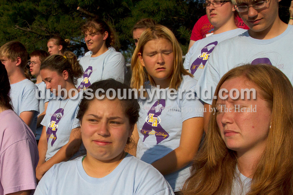 Olivia Corya/The Herald<br /> Heritage Hills marching band members Jazmín Stevens, bottom left, freshman, Ashley Gentry, right, sophomore, and Jay Webb, senior, next row up between the other two, held their breath as they waited for their placement to be announced after their performance at the ISSMA band districts at Jerry Brewer Alumni Stadium in Jasper on Saturday. Their school placed gold.