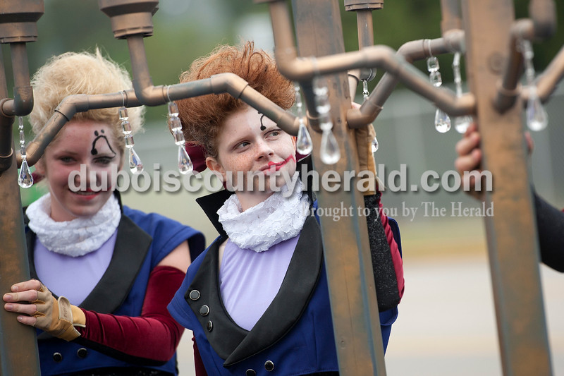 """Olivia Corya/The Herald<br /> Southridge color guard members Paige Michel, right, and Paige McCarty, both freshman, dressed up as mad composers to fit their marching band's """"twisted classics"""" theme, waited for their turn to perform at the ISSMA band districts at Jerry Brewer Alumni Stadium in Jasper on Saturday."""