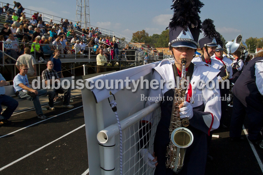 Olivia Corya/The Herald<br /> Heritage Hills freshman Olyvia Blessinger wetted the reed on her alto saxophone as she waited with her marching band to compete in the ISSMA band districts at Jerry Brewer Alumni Stadium in Jasper on Saturday.