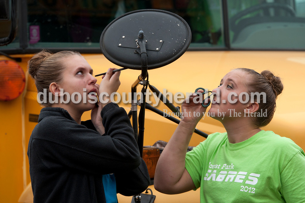 Olivia Corya/The Herald<br /> Forest Park color guard members Tiffany Singer, junior, left, and Kelsey Nordhoff, senior, applied makeup and curled their eyelashes in a school bus mirror before competing at the ISSMA band districts at Jerry Brewer Alumni Stadium in Jasper on Saturday.