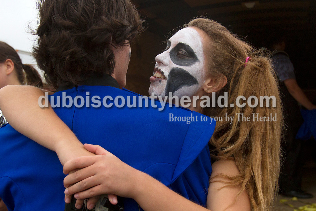 Olivia Corya/The Herald<br /> Northeast Dubois drum major Nikki Faulkner, dressed up for her marching band's psychotic carnival theme, hugged her boyfriend Willie Canary after their band's performance at the ISSMA band districts at Jerry Brewer Alumni Stadium in Jasper on Saturday. Both are juniors.
