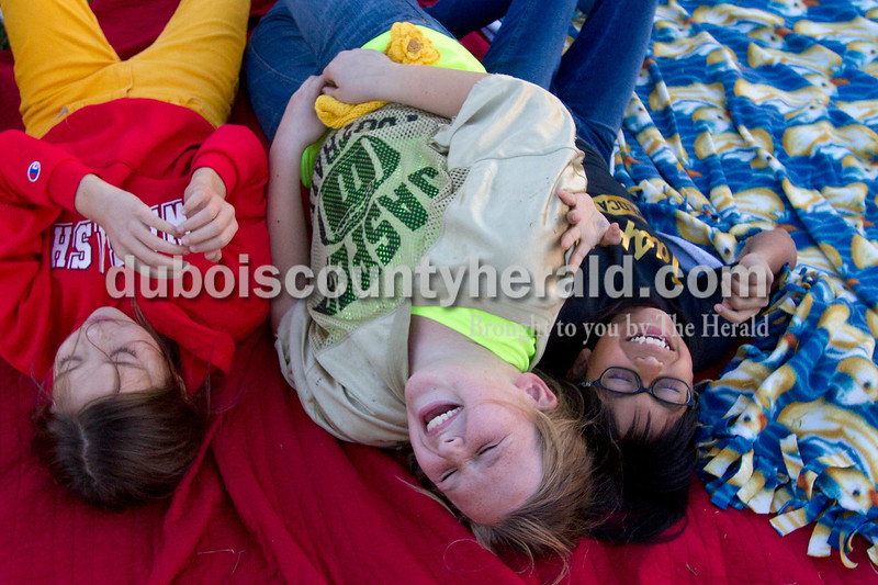 "Olivia Corya/The Herald<br /> Annie Donato, 10, Laura Gobert, 10, and Kimber Schnarr, 11, left to right, giggled as Laura's little sister, not pictured, jumped on them as they waited for the movie Horton Hears a Who to start during Tenth Street Elementary's first annual ""Screen on the Green"" event behind the school on Friday evening. All the girls live in Jasper."