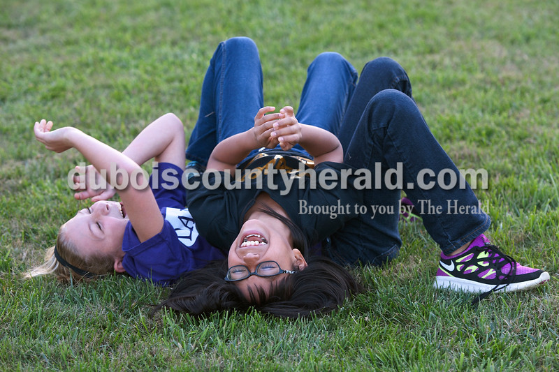 "Olivia Corya/The Herald<br /> Kaitlyn Henke, 10, and Kimber Schnarr, 11, both of Jasper, played around while they waited for the movie Horton Hears a Who to start during Tenth Street Elementary's first annual ""Screen on the Green"" event behind the school on Friday evening. The friends are in fifth grade together at Tenth Street Elementary."
