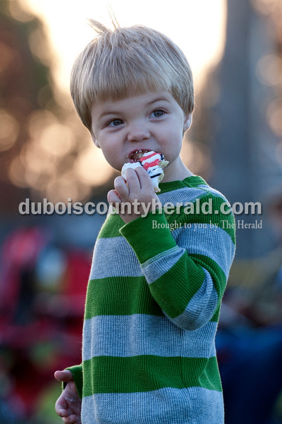"Olivia Corya/The Herald<br /> Brandon Buse of Huntingburg, 2, munched on a cat in the hat cookie as he waited with his family for the movie Horton Hears a Who to start during Tenth Street Elementary's first annual ""Screen on the Green"" event behind the school on Friday evening. Brandon's mom Stephanie Buse is a teacher at the school."