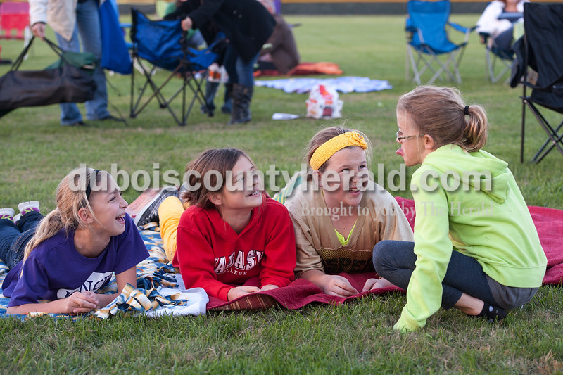 "Olivia Corya/The Herald<br /> Kaitlyn Henke, Annie Donato, and Laura Gobert, left to right, all 10, giggled as Laura's sister Julia Gobert, 9, stuck her tongue out while they waited for the movie Horton Hears a Who to start during Tenth Street Elementary's first annual ""Screen on the Green"" event behind the school on Friday evening. The girls are all from Jasper."