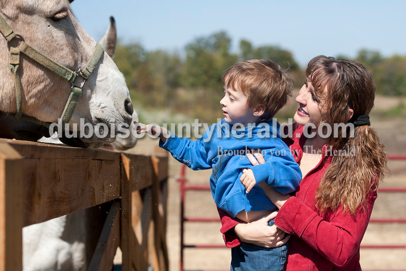 "Olivia Corya/The Herald<br /> Vincennes University Jasper Campus professor Angie Mayfield of Haysville helped her son Tucker, 3, reach one of their mules at their stable near Haysville before they took them riding at Hoosier National Forest on Friday afternoon. She said she loves spending time with her animals; ""It's a stress reliever. When I'm not in the classroom I'm out on the trail riding my mule."" She also said her country-girl background--""I deer hunt, I like to ride, I like to be outdoors""--helps her connect with her students, many of whom come from rural areas."