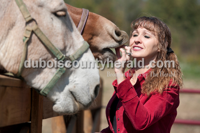 "Olivia Corya/The Herald<br /> Vincennes University Jasper Campus professor Angie Mayfield of Haysville fed apple and alfalfa flavored treats to her mules at her stable near Haysville before she and her family took them riding at Hoosier National Forest on Friday afternoon. She said she loves spending time with her animals; ""It's a stress reliever. When I'm not in the classroom I'm out on the trail riding my mule."" She also said her country-girl background--""I deer hunt, I like to ride, I like to be outdoors""--helps her connect with her students, many of whom come from rural areas."