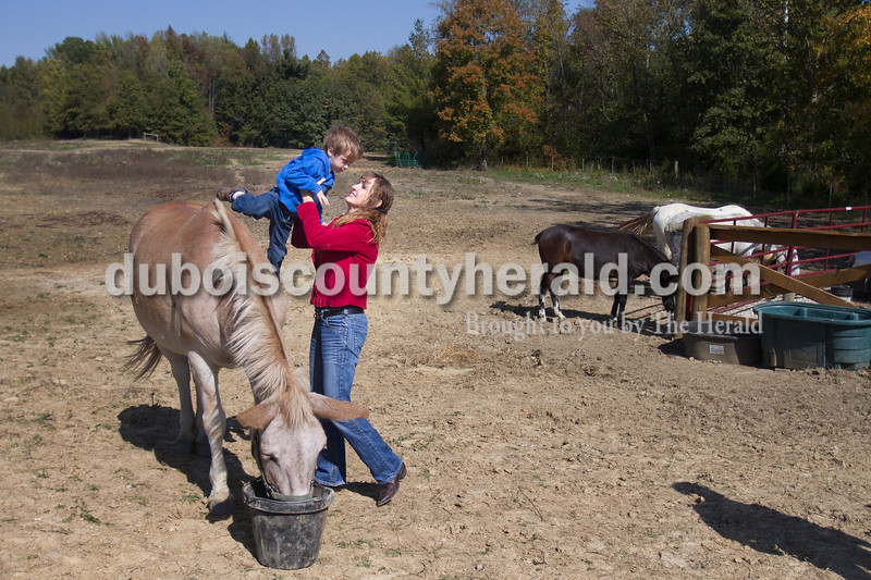 "Olivia Corya/The Herald<br /> Vincennes University Jasper Campus professor Angie Mayfield of Haysville helped her son Tucker, 3, hop off one of their mules at their stable near Haysville before they took them riding at Hoosier National Forest on Friday afternoon. She said she loves spending time with her animals; ""It's a stress reliever. When I'm not in the classroom I'm out on the trail riding my mule."" She also said her country-girl background--""I deer hunt, I like to ride, I like to be outdoors""--helps her connect with her students, many of whom come from rural areas."
