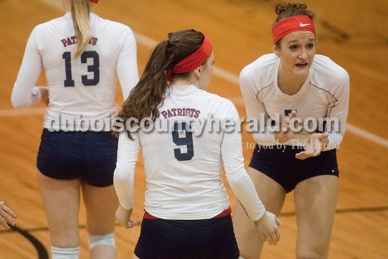 Rachel Mummey/The Herald<br /> Heritage Hills' Madison Fella, right, encouraged her teammates with Miriah Leibering, center, and Kaebra LaGrange during their match against Jasper in the Class 3A volleyball sectional championship at Cabby O'Neill Gymnasium on Saturday.