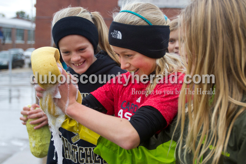 Olivia Corya/The Herald<br /> Regan Mundy of Jasper, 11, squeezed extra water out of a sponge next to Madalin Dant of Washington, 11, as they participated in a car wash fundraiser for their soccer team in a parking lot on W 4th Street in Jasper on Saturday. Because of the summer's drought and water restrictions, they had to push back the date on their second annual event until the chilly fall day. They said the hard work kept them warm.