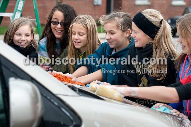 Olivia Corya/The Herald<br /> Kendall Russ, 11, Jessica Cruz, 11, Jenna Spray, 11, Mackenzie Cooley, 12, Madalin Dant, 11, and Mary Kate Hopf, 11, all of Jasper except Madalin, who is from Washington, scrubbed an SUV in a parking lot on W 4th Street in Jasper during a car wash fundraiser for their soccer team on Saturday. Because of the summer's drought and water restrictions, they had to push back the date on their second annual event until the chilly fall day. They said the hard work kept them warm.
