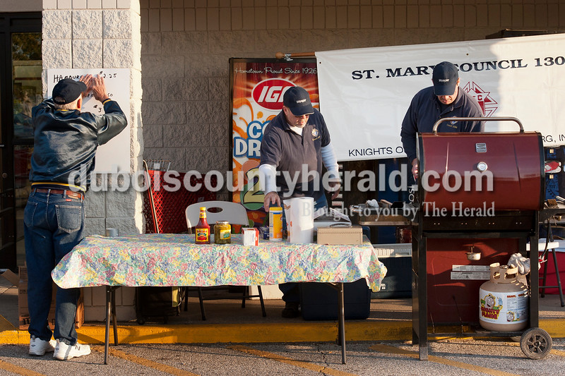 Olivia Corya/The Herald<br /> Knights of Columbus members John Kiefer of Huntingburg and brothers Kevin Kreilein of Huntingburg and Steven Kreilein of Ireland, left to right, set up a barbecue fundraiser for their organization outside the Huntingburg IGA on Saturday morning. The three men are the only remaining members of St. Mary's Knights of Columbus, the group's Huntingburg chapter.