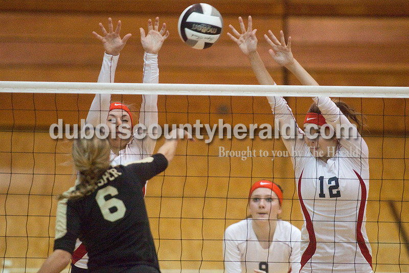 Rachel Mummey/The Herald<br /> Heritage Hills' Abby Fischer and C.J. Nance tried blocking a spike by Jasper's Annie Huebner during their match against Jasper in the Class 3A volleyball sectional championship at Cabby O'Neill Gymnasium on Saturday.