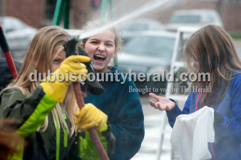Olivia Corya/The Herald<br /> Mackenzie Cooley, 12, laughed as Jenna Spray, 11, spritzed another friend with water during a car wash fundraiser for a girls soccer team in a parking lot on W 4th Street in Jasper on Saturday. Standing next to Mackenzie is Mary Kate Hopf, 11. All girls are from Jasper. Mackenzie isn't on the soccer team, but lots of her friends are so she came to help.