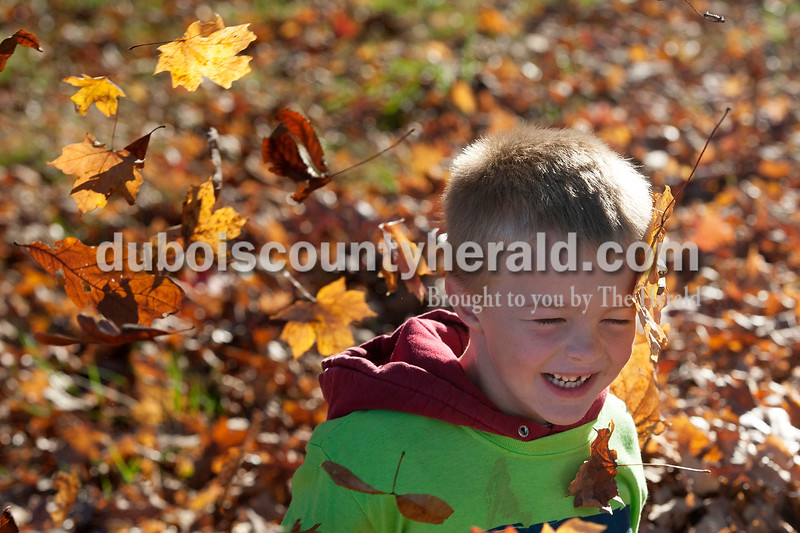 Olivia Corya/The Herald<br /> Eli Meece of Huntingburg, 6, aimed a toy gun as he crouched behind a leaf bunker outside Zoar United Methodist Church in Holland on Saturday. He was waiting for bikers to finish a bike-a-thon organized by the church that was the final event in a series of fundraisers for the Lange-Fuhs Cancer Center Patient Emergency Fund.