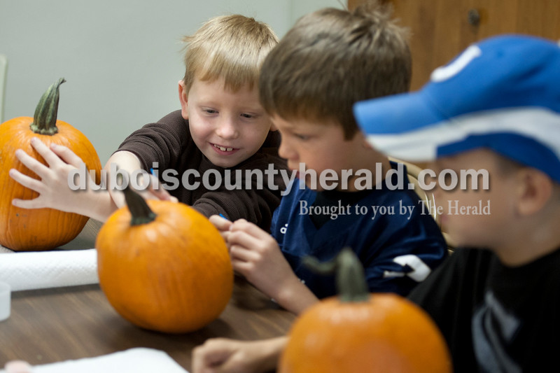 "Olivia Corya/The Herald<br /> Friends Parker Rehms, left, Owen Morrison and Luke Ramsey, all of Huntingburg, 7, planned how they would paint their pumpkins during a pumpkin decorating party at the Huntingburg Public Library on Saturday. Parker chose to paint a ""Dracula with diamonds,"" Owen created a ""half water, half fire snake"" design, and Luke adorned his with a painting of a cave."