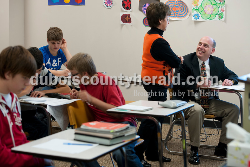 "Olivia Corya/The Herald<br /> Jason Schmitt of Jasper, who is an alumnus of Jasper High School and Vice President of loans at Springs Valley Bank, sat in on a geometry class instructed by his former algebra teacher Brenda Wagner when he returned to his old school as ""Principal for a Day"" on Wednesday. Schmitt shadowed Principal Brian Wilson, learned how to evaluate teachers, and supervised the lunch room during the high school's first of two such events. The second ""Principal for a Day"" event will be in December. The students in the foreground, from left, are sophomore Kaden Gosman, freshman Caleb Dosch, sophomore Asher Saare, and freshman Matthew Britzman."